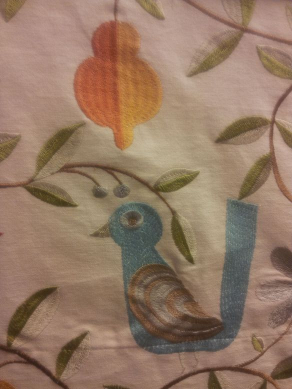Cartoon bird, embroidered on a linen fabric